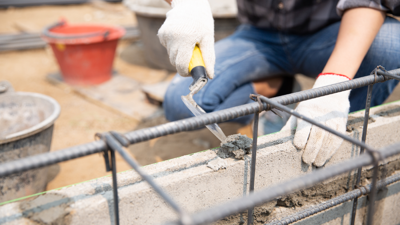 bricklayer-worker-installing-brick-masonry-on-exterior-wall-with-trowel-putty-knife